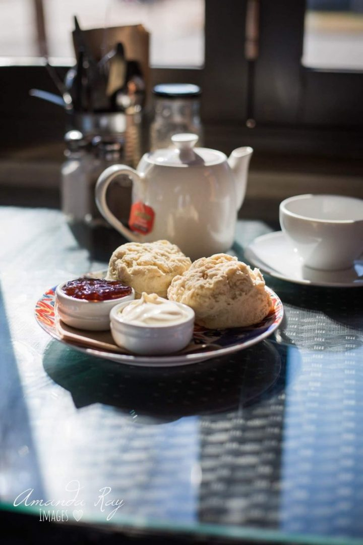 Cafe table set with plate of scones with jam and cream and pot of tea in background